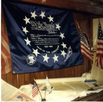 """Image of Print, Photographic - Color photo of a display case containing flags and blue """"We The People"""" banner."""