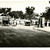 Image of Print, Photographic - B&W panoramic photo showing Tent City with a band standing in the street in front of the Tent City Office.