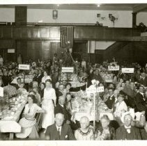 Image of Print, Photographic - B&W photo showing a large group of people seated at tables at the States Dinner in the Atascadero community bldg (Federated Church).   Signs with the names of the different states can be seen on each table.
