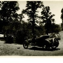 Image of Print, Photographic - B&W panoramic photo showing an old car at center.  Drainage pipes can be seen at both sides of photo.  A tent can be seen through the trees in background.  Possible construction camp.