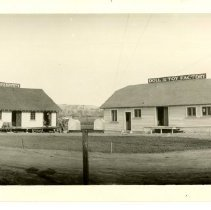 """Image of Print, Photographic - B&W panoramic photo showing the Atascadero Doll and Toy Factory with two old cars parked in front.  A building can be seen at left with a sign on the roof that reads """"Rapid Photo Equipment""""."""