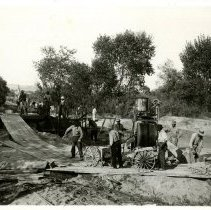 "Image of Print, Photographic - B&W photo showing a group of men working with a cement mixer and wheel barrels.  Note on the back reads ""Building concrete bulwarks in the bed of the Salinas River to protect the wells.""."