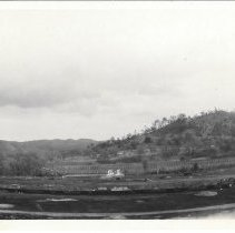 Image of Print, Photographic - B&W panoramic photo showing a railroad train traveling past 3 small warehouses.  Pine Mountain can be seen in the background.