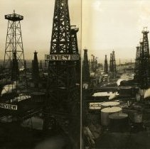 """Image of Print, Photographic - B&W panormic (4 fold) photo showing an oil field with many oil wells and oil tanks. 3 of the derricks have a sign on them that reads """"Review""""."""