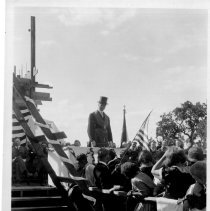 Image of Print, Photographic - B&W photo showing a man in a top hat giving a speech on a stage surrounded by people the Masons at Atascadero high school.
