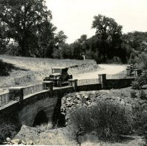 "Image of Print, Photographic - B&W photo showing a vintage auto driving over a culvert with a fancy iron railing - circa early 1920s.  ""California Illustrated Review"" is printed on the door of the car."