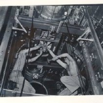 Image of 07.49.6 - Two unknown men working inside a B-29's bomb bay on Tinian.