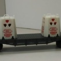 "Image of 14.42.24 - 36006 Black flat with2 lit glow-in-the-dark uranium canisters.  Canisters read ""AEC DANGER URANIUM.""  Car reads ""Built 1999 by Lionel, RADIOACTIVE, AEC, TRANSPORT, 6805,""