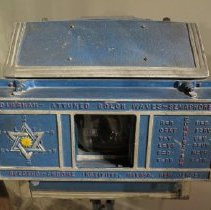 Image of 04.29.44 - Blue metal box attached to metal stand, Spectro-Chrome Electrostatic X-Ray Machine. Has viewing port and controls. Has star shape on front which showed the direction of various colors of light.