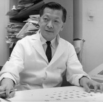 Image of Dr. Joe Hin Tjio at his desk with photograph of chromosomes