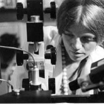 Image of National Cancer Institute - Technician in pathology lab studying cancer cells