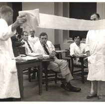Image of Jerry Hecht Digital Collection - Dr. Nina Braunwald and surgical team examining printout of heart processes