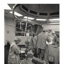 Image of Jerry Hecht Digital Collection - Nina Starr Braunwald views an instrument while surgery continues