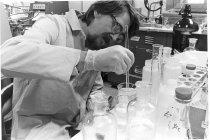 Image of National Cancer Institute - Lab scientist prepares media in hot virus lab