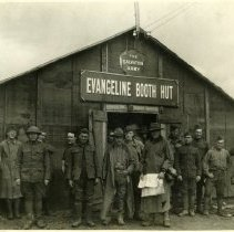 """Image of A 7.75""""x9.75"""" black and white photograph of a group of United States' soldiers standing outside of a wooden building.  The building has a sloped roof.  A sign above the door reads, """"EVANGELINE BOOTH HUT.""""  Above the sign there is a Salvation Army crest."""