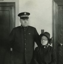 """Image of A 7.75""""x9.875"""" black and white photograph of """"Envoy and Mrs. Stufflebeam,"""" both wearing full Salvation Army uniform.  Mrs. Stufflebeam is seated with her hands folded in her lap.  She is wearing glasses.  Mr. Stufflebeam is standing with his hand resting on his wife's back.  The back of the photo reads as follows: """"Envoy and Mrs. Stufflebeam transferred to the Hawaiian Islands July 1931.  Mrs. Stufflebeam was formerly known as Adjt. Margaret Sheldon who made the first doughnut in France during World War I."""""""