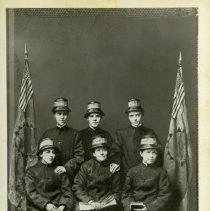 """Image of A black and white photograph of six of the """"splendid seven.""""  The term """"splendid seven,"""" refers to the seven female Salvationists who first came to the United States of America on March 10,1880.   The women were led by George Scott Railton, and their group's arrival in New York made them the first officially authorized Salvation Army forces to reach the American continent.  In the photograph, three of the women are seated in a row, while the other three stand behind them.  All three of the seated women are holding books and/or papers.  Modified American flags flank the group on either side."""