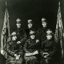 """Image of Two (2) copies of a black and white photograph of six of the """"splendid seven.""""  The term """"splendid seven,"""" refers to the seven female Salvationists who first came to the United States of America on March 10,1880.   The women were led by George Scott Railton, and their group's arrival in New York made them the first officially authorized Salvation Army forces to reach the American continent.  In the photograph, three of the women are seated in a row, while the other three stand behind them.  All three of the seated women are holding books and/or papers.  Modified American flags flank the group on either side."""