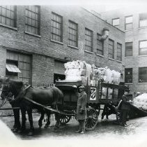 """Image of This is an 8""""x10"""" black and white photograph of a large wagon drawn by two horses.  The wagon is being loaded with large piles of paper.  The paper appears to be old newsprint, perhaps on its way to being recycled.  A Salvation Army officer stands at the side of the wagon looking at something held in his hand, while a group of three men use a ramp to load the next pile of paper onto the wagon.  The original catalog describes the wagon as a """"Salvation Army paper salvage wagon."""""""