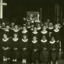 """Image of A 4.25""""x6.25"""" black and white photograph of the Lytton Children's Choir.  Lawrence and Wilma Smith flank the group on either side.  There are three rows of children, both boys and girls.  The children are wearing traditional choir robes."""