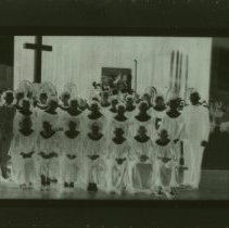 """Image of A 4""""x5"""" black and white negative of the Lytton Children's Choir.  Lawrence and Wilma Smith flank the group on either side.  There are three rows of children, both boys and girls.  The children are wearing traditional choir robes."""