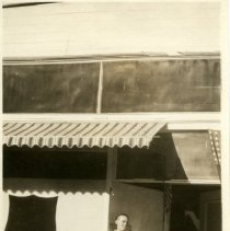Image of Picture of a boy standing under an awning adjacent to the silouhette of an SA shield.