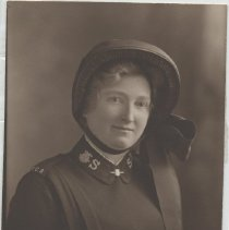 """Image of A portrait of an unidentified female Salvation Army officer, wearing epaulets that say """"T.C.S""""."""