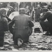 Image of A snapshot of uniformed Chinese Salvation Army officers kneeling on a cobblestone street.