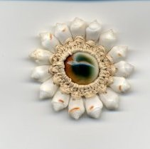 Image of A pin made of 15 shells with a stone in the center.  The shells are held together by macrame and was made by a youth from the Marshall Islands which is a Micronesian nation. -