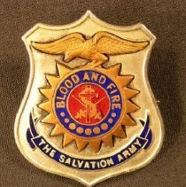 Image of A metal pin of the Salvation Army shield with the Salvation Army Crest in the center. -