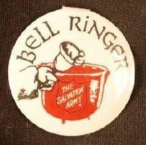 """Image of A circular pin with a picture of a Salvation Army Christmas kettle with the inscription """"Bell Ringer"""" above it. -"""