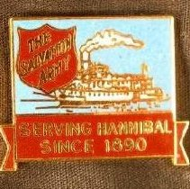 """Image of A square pin with the Salvation Army shield in the corner and the picture of a steamboat in the center. There is writing at the  bottom of the pin which reads """"Serving Hannibal Since 1890."""" -"""