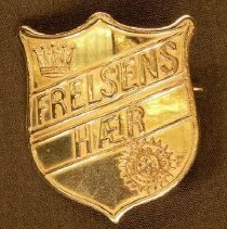 Image of A metal pin in the shape of the Salvation Army crest with an  inscription in a foreign language. -
