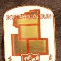 Image of A metallic pin with the picture of the states of Utah, Colorado, Wyoming and Montana and the Salvation Army shield. The pin represents the Salvation Army's Intermountain Division in the Western Territory. -