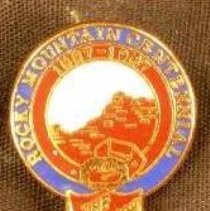 Image of A pin with a picture of a mountain range with the Salvation Army shield below it. The pin celebrates the 100th anniversay of the Salvation Army in the Rocky Mountain area. -