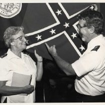 Image of A digital copy of an 8x10, B&W photograph of Comm. Joan Miller and Major Ed Covert holding a Confederate flag.