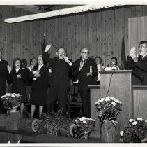 Image of A digital copy of an 8x10, B&W photograph of officers singing and cheering on stage during camp meetings at Redwood Glen.