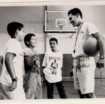 Image of A 8x10 photo of a basketball coach with a group of children.