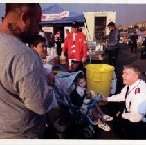 Image of A photograph of Major Mike Dickinson speaking with a family while providing food and drink during a disaster.
