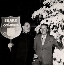 Image of A B&W photograph of Lt. Colonel Donald Barry standing with television personality and talk show host Lawrence Welk in an attempt to raise awareness of The Salvation Army Christmas Kettles.