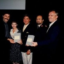 Image of A photograph of Major Joe Noland with four unidentified celebrities holding what appears to be videotapes.