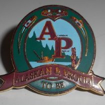"""Image of A pin with a boat, water, trees and a totem pole with the words, """"Alaskan & Proud To Be."""" -"""