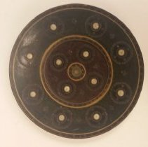 Image of A black and red lacquered plate with red and gold detailing. -
