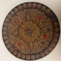 Image of A large bronze, blue, and red mandala with a flower pattern in the center.  -