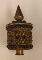 Image of An ornate bauble of sorts, it looks to be either Hindu Arabic or Byzantium style. In it are various colored beads of glass and the top has a mandala of a flower -
