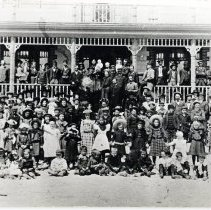 """Image of A B & W photograph of Amity's Cherry Tree Home - Orphanage. """"Most modern building of its time in area, name is from Cherry Orchard."""" (4 copies)  Far left, 3rd over: Elizabeth Childs """"Duer"""", Lt. Col. Duer's brother's wife Third over, standing: Alice Erickson Female officer in center, ruffles: Richie Ruff married the D.O. in charge of Amity Wearing a black dress: Mabel Fleming Wearing a striped dress in front: Aunt Annie"""
