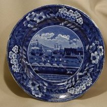 Image of 1967.001.025 - Blue transferware plate of the Landing of General Lafayette. Impressed Makers Mark unclear. Painted under glaze: H C  B19/66  and number  9. Other Marking unclear.