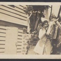 Image of Woman with a saddled horse - circa 1925