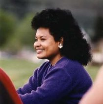 "Image of 90's Student, Woman - ""Foreign Students""  This is a color snapshot of a young woman with dark, curly hair.  She is wearing a long sleeved sweater, jeans and round silver earrings."
