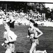 """Image of 1992 Cross Country Running 1 - """"1992 - X-Country""""  Two """"EASTERN OREGON"""" young women run on the track in the EOSC Stadium.  A large crowd of fans watches from the stadium seating in the background."""